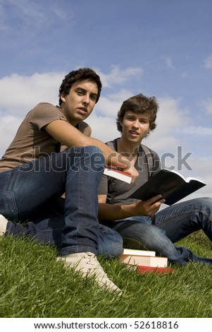 Two college or university students studying on the park