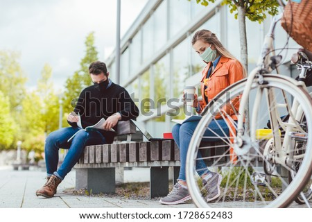 Two college students learning while keeping social distance on campus ストックフォト ©