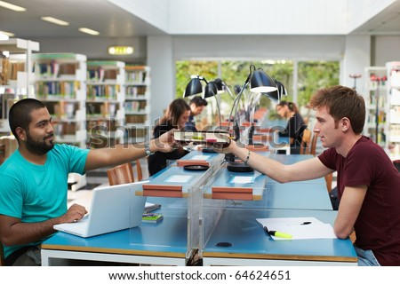 two college students sitting in library with laptop computer and sharing book. Horizontal shape, side view, copy space