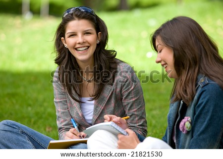 two college students smiling outdoors looking very happy