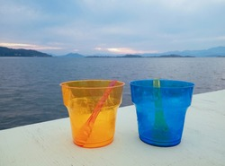 Two colored transparent plastic cups empty after sorbet and ice cream, with spoons inside, on the wooden white table, evening beach in the background. Summer vacation, refreshment concept