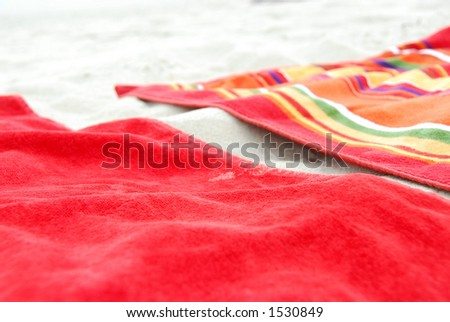 Two colorful beach towels on sandy beach