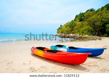 Two colorful canoe on sandy beach by crystal blue sea in Phuket, Thailand