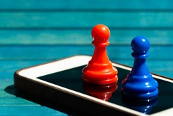 Two colorful chess pawns, red and blue colored game pieces standing on top of a modern smartphone screen, display closeup. Mobile phone app development, mobile gaming simple abstract concept, nobody