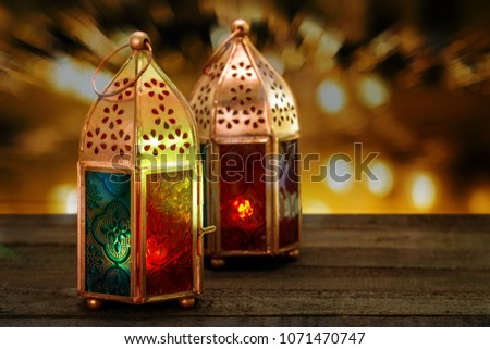 Two colorful oriental Lamp lanterns burn with candles with colorful bokeh background for Ramadan and other islamic muslim holidays, space for text #1071470747