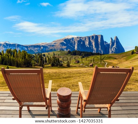 Two comfortable lounge chairs on the hotel terrace. Alpe di Siusi is charming plateau in the Dolomites. Wonderful holiday in the fresh air. The concept of walking, ecological and photo tourism