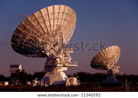two compact array radio telescopes photographed at sunset