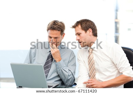 Two concentrated businessmen working together on a laptop in the office
