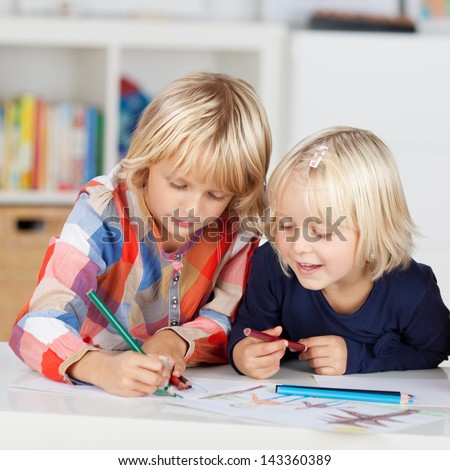 Two Concentrated little girls drawing on paper at table
