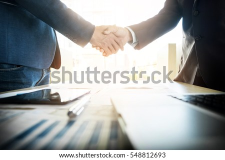 Two confident business man shaking hands during a meeting in the office, success, dealing, greeting and partner concept. #548812693