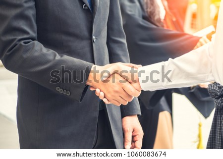 Two confident businessman shaking hands during in meeting room to agreement new success work,