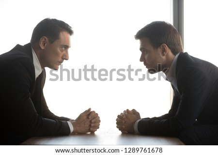 Two confident businessmen with clasped hands look at each other sitting opposite as rivalry confrontation concept, business opponents competitors politicians debate, difficult negotiations, side view
