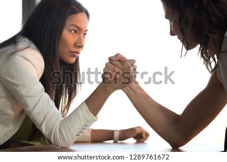 Two confident diverse businesswomen compete arm wrestling look in eyes feel jealous envious about success, young asian and caucasian female rivals armwrestling struggle for leadership rivalry concept #1289761672
