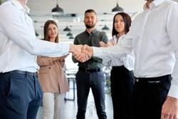 two confident male entrepreneurs in formal clothes suit shaking hands after agreement, make contract. mutual business deal. Side view close-up hands. business people. colleagues clapping hands