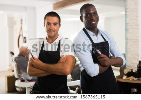 Two confident professional barbers standing in hair salon holding hairdressing tools in hands
