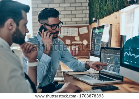 Two confident young modern men in formalwear working using computers while sitting in the office Zdjęcia stock ©