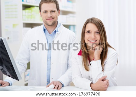 Two confident young pharmacists at work with the man working on the computer as the woman leans forwards over the counter with a smile