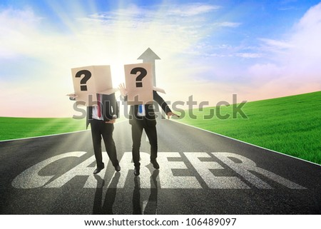 Two confused businessman finding the career path with heads covered by cardboard - stock photo