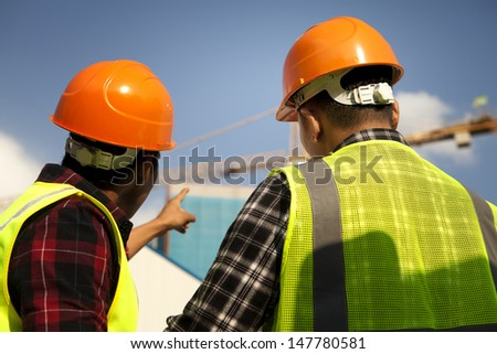 Two construction worker wearing safety vest discussion looking and pointing yellow crane at construction site