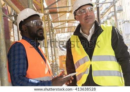 Two construction workers, a black and a white, wearing orange and yellow safety jackets and helmets among scaffolding on construction site