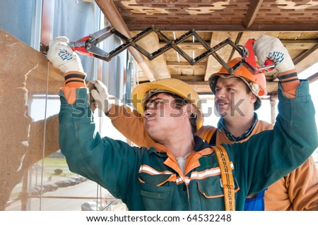 Two construction workers builders riveting big tile on a building facade