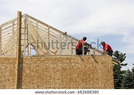 Two construction workers on the roof of a house being built. #682688380