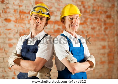 Two construction workers standing in a constrcution site in front of a war brick wall. Their arms are folded and they are wearing hardhats