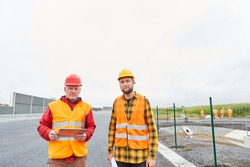 Two construction workers with tablet computers on the construction site in road construction in the new development area