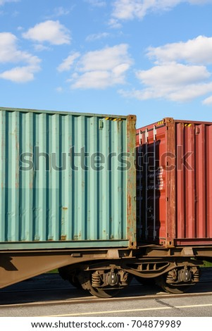 Two containers on a flat car train parked in a shipping yard in the region of Paris, France.