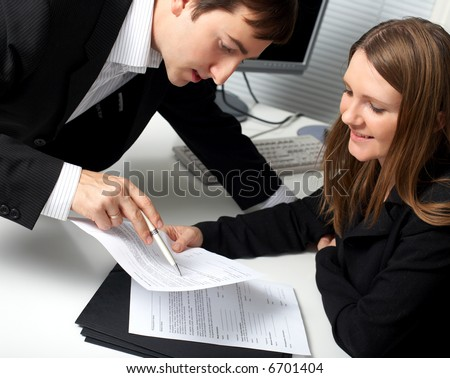 Two contemporary businesspeople discussing a document