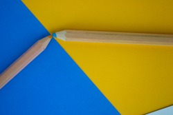 Two contrasting pencils meet on a bright colored background. Minimalist design with lots of room for text. Contrasting colors meeting.