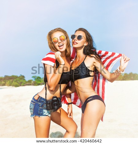 Two cool trendy hipster girls at the beach enjoying vacation on a tropical island, perfect tanned body, sexy stylish casual wear, bikinis, blonde and brunette with the camera, woman photographer