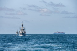 Two corvette warships sail together in the sea with container ship on the horizon.