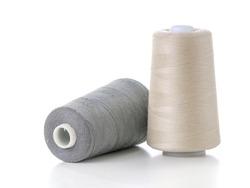Two cotton thread spools on white