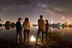 Two couple having a rest on lake shore near bonfire together. Friends enjoying beautiful view of night sky full of stars and Milky way, quiet water surface and luminous town on background.