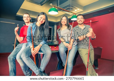 Two couples having fun at billiard - Group of multiracial young people standing next to pool table and holding cue - Students spending an evening at pub
