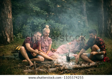 Two couples having picnic in woods. Bearded man and his best friend cooking sausages over fire. Young hikers around campfire in the evening. Friendship and leisure concept. #1105574255
