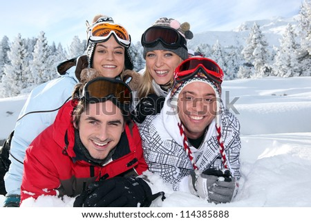 Two couples laying in the snow