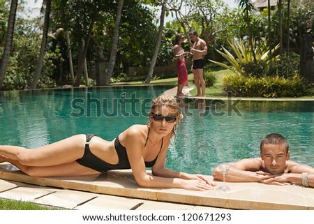 Two couples lounging and relaxing by the edge of a swimming pool in a tropical destination hotel spa garden while on vacations.