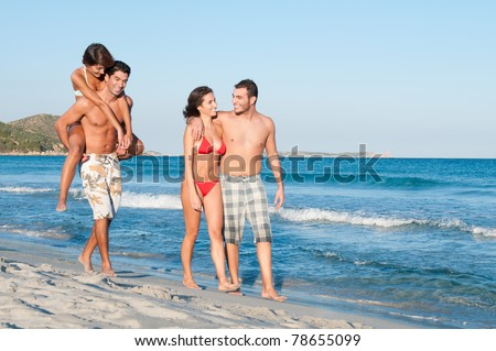 Two couples of friends walking along the beach in a summer vacation day