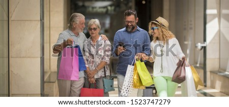 two couples of two adults and two seniors go shopping together at the mall with a lot of bags with clothes and more on their hands - four people - man with phone #1523747279