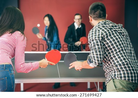 Two couples of young people playing ping pong in a hostel - Four students with ping pong paddles having fun in a pub