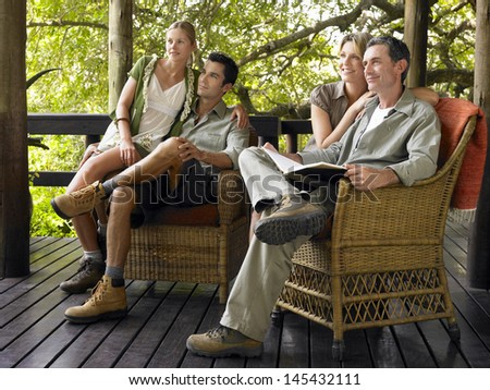 Two couples sitting in wicker chairs on terrace #145432111