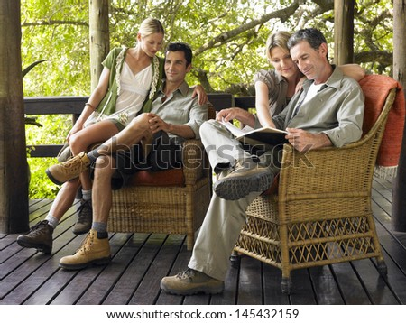 Two couples sitting in wicker chairs on terrace #145432159