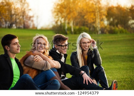 Two couples sitting on the loan in the park smiling and having fun