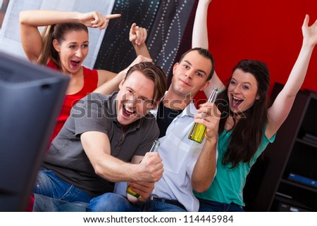 Two couples watching sports in the telly, they all are really excited, drink beer and cheer their team - stock photo