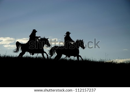 Two cowboys silhouetted against a Montana dawn sky