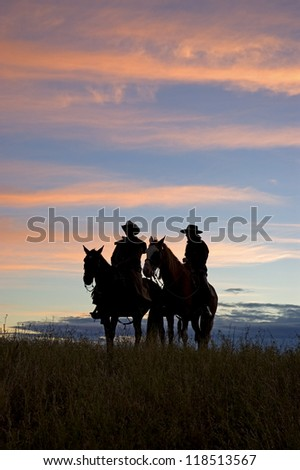 Two cowboys silhouetted against dawn sky,Montana