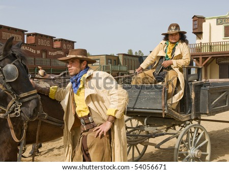 Two cowboys waiting with a wagon