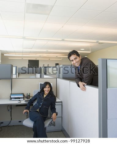 Two coworkers in office cubicles